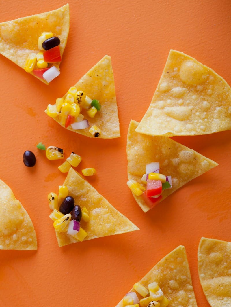 A close up of grilled corn salsa on tortilla chips.