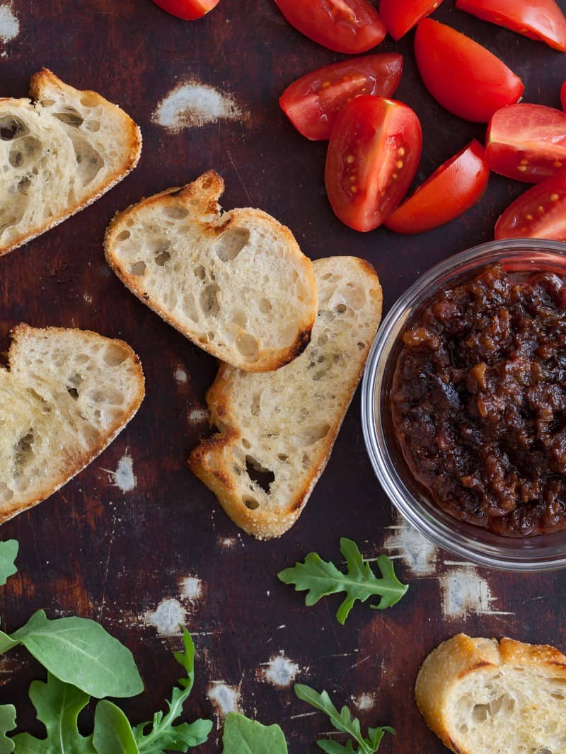A close up of crostini with tomatoe wedges and a bowl of boozy bacon jam.