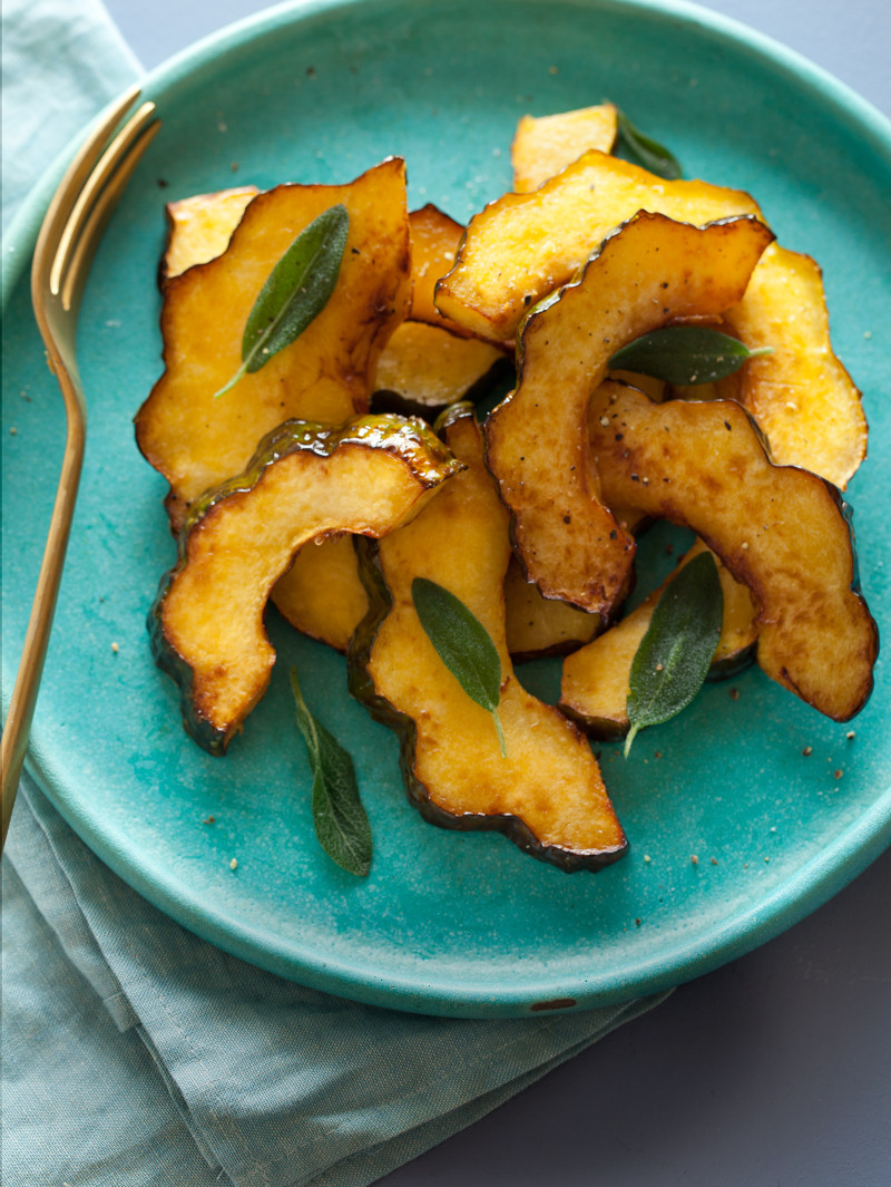 Maple glazed roasted acorn squash on a turquoise plate with a fork.