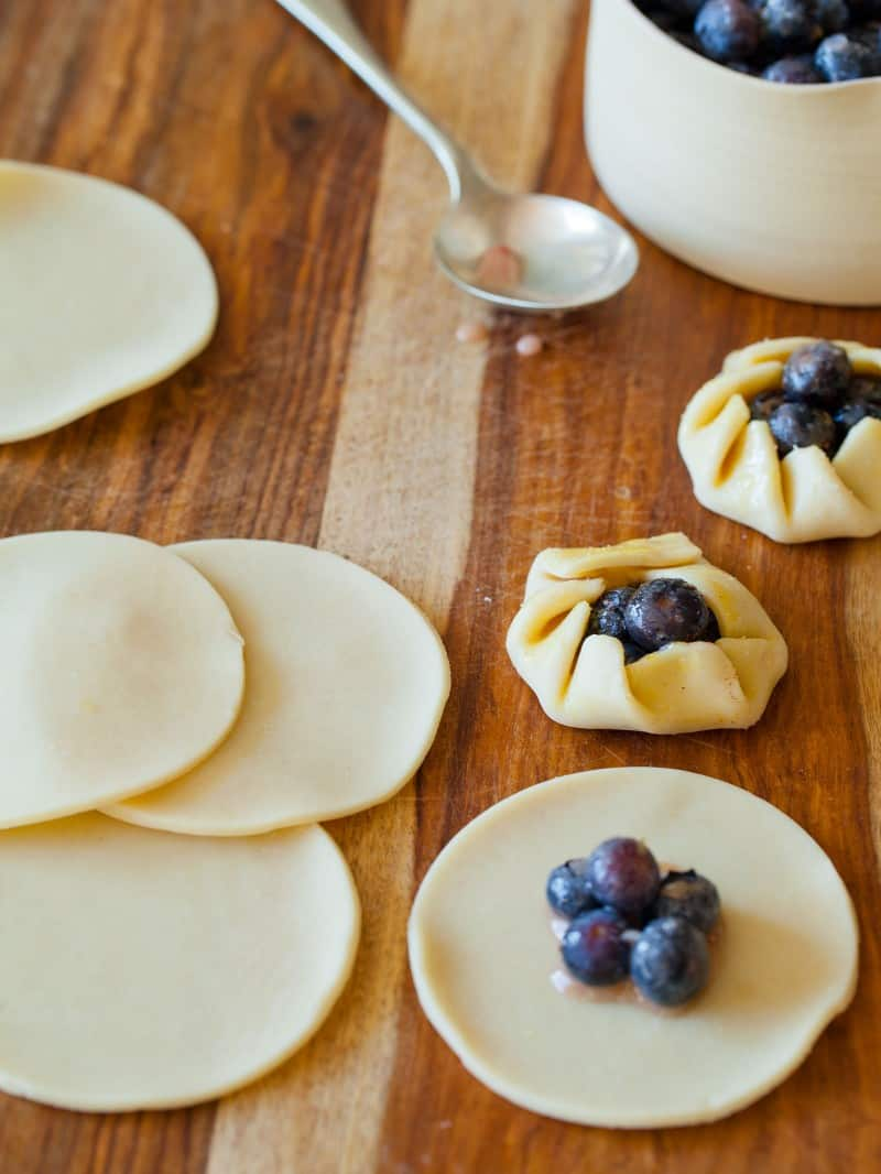 A close up of mini blueberry galettes being assembled with a spoon.