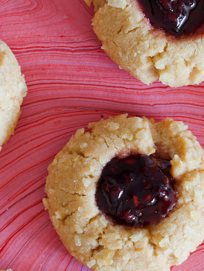 A close up of peanut butter and jelly potato chip thumbprint cookies on a pink surface.