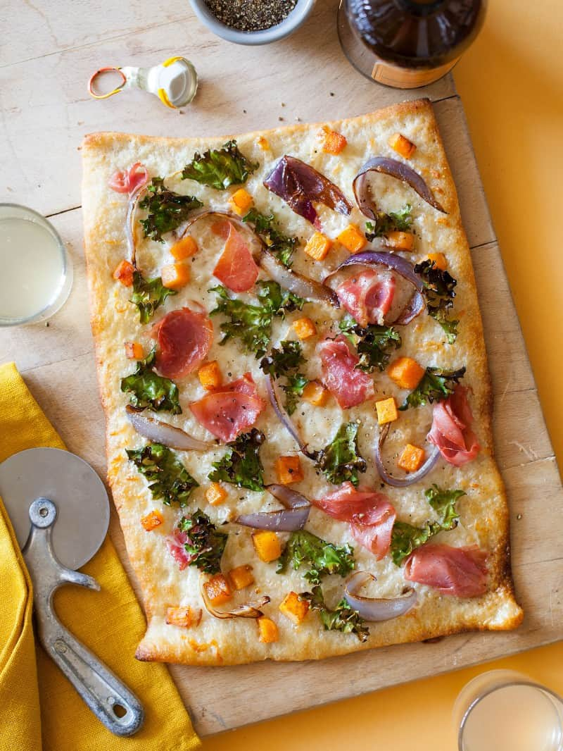 Prosciutto kale butternut squash pizza on a wooden cutting board with a pizza cutter and drink.