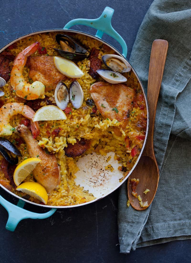A pot of paella with a serving taken out and a wooden spoon.