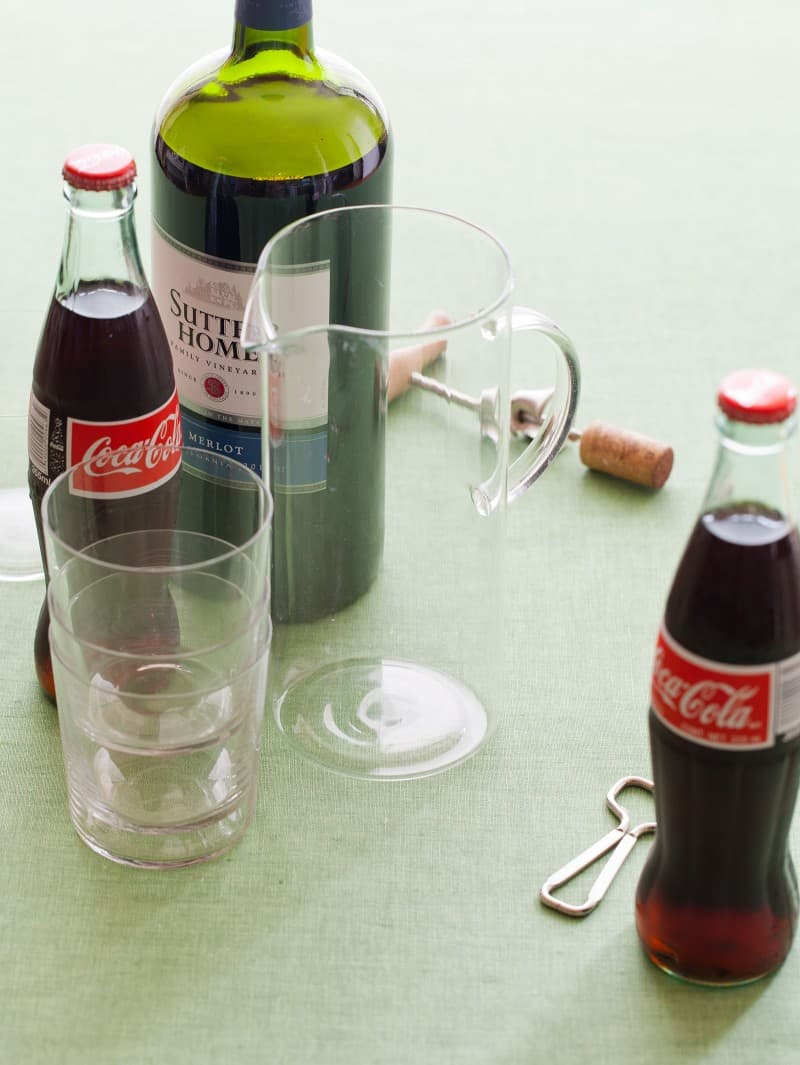 Ingredients for kalimotxo with a glass pitcher, empty glasses, and bottle openers.