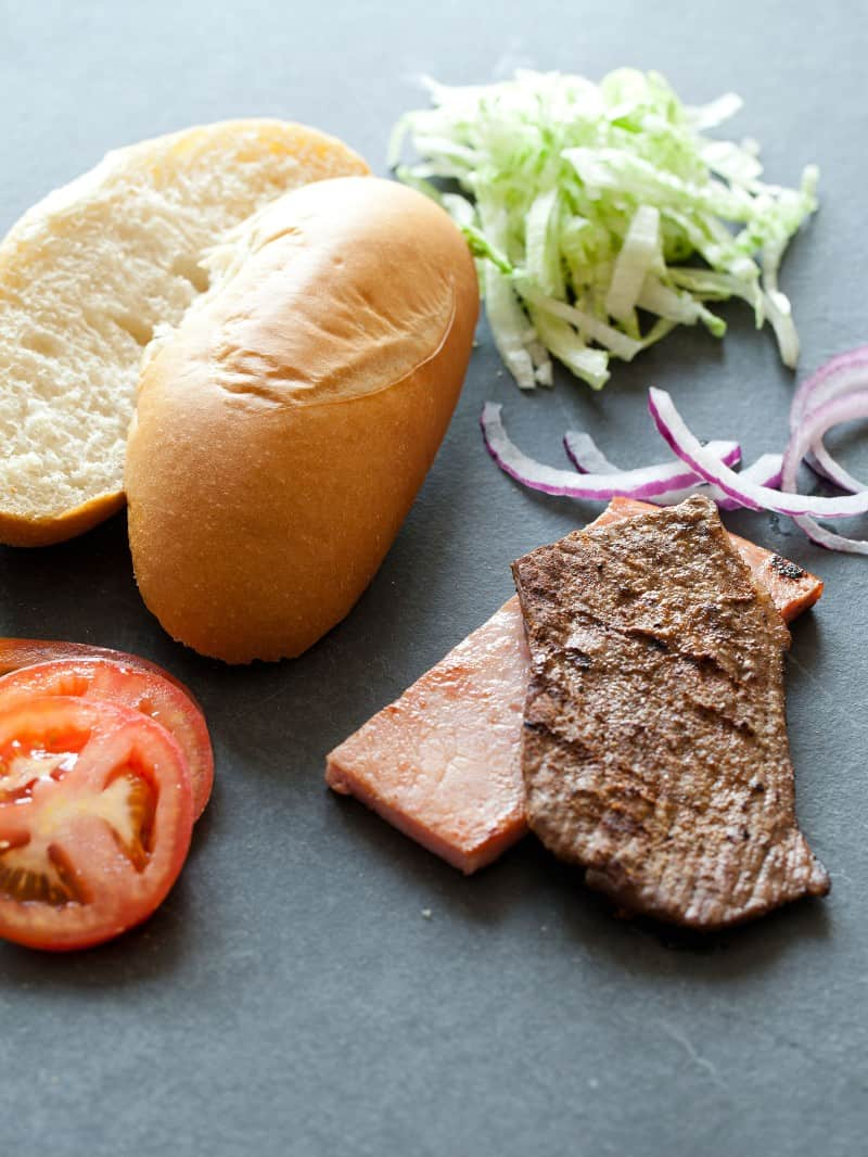 Chivito ingredients. Steak, ham, lettuce, bun, onions, and tomatoes.