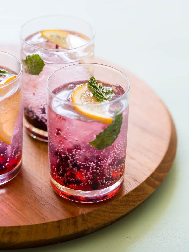 A close up of blackberry and meyer lemon gin and tonics on a wooden board.