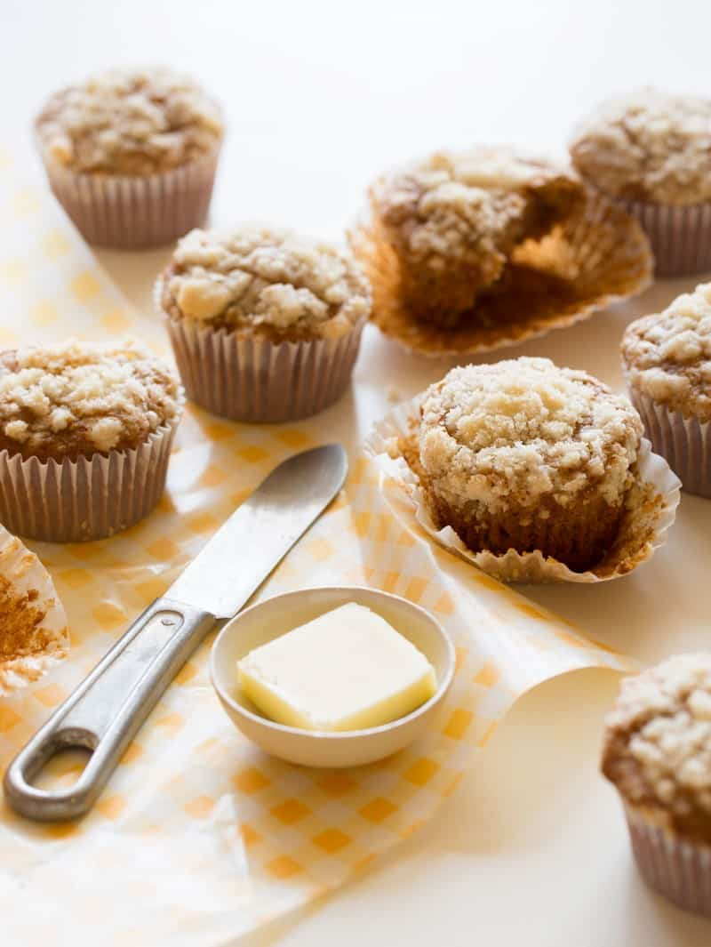 Several streuseled acorn squash muffins next to a ramekin of butter and a knife.