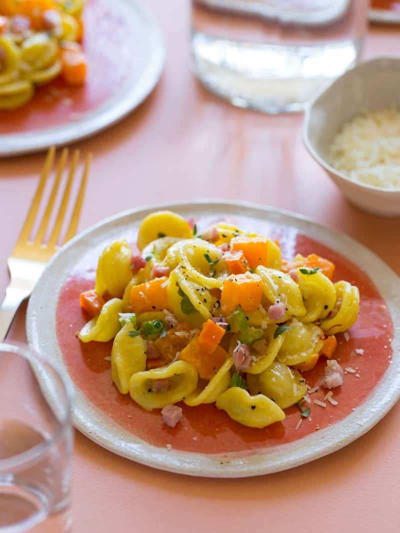 A close up of a plate of butternut squash and pancetta orecchiette with a fork.