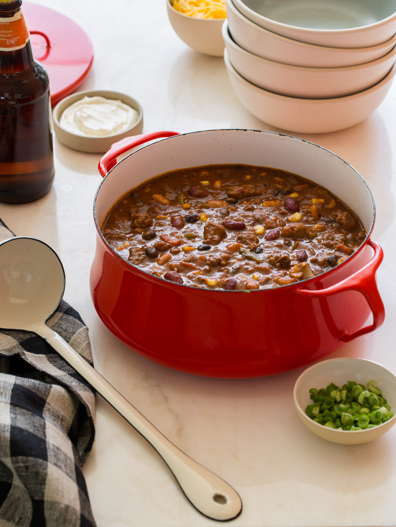 A red pot of kitchen sink chili with bowls, a ladle, and toppings on the side.