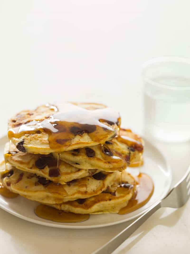 A stack of chocolate chip, bacon, orange zest pancakes drizzled in syrup with a fork.