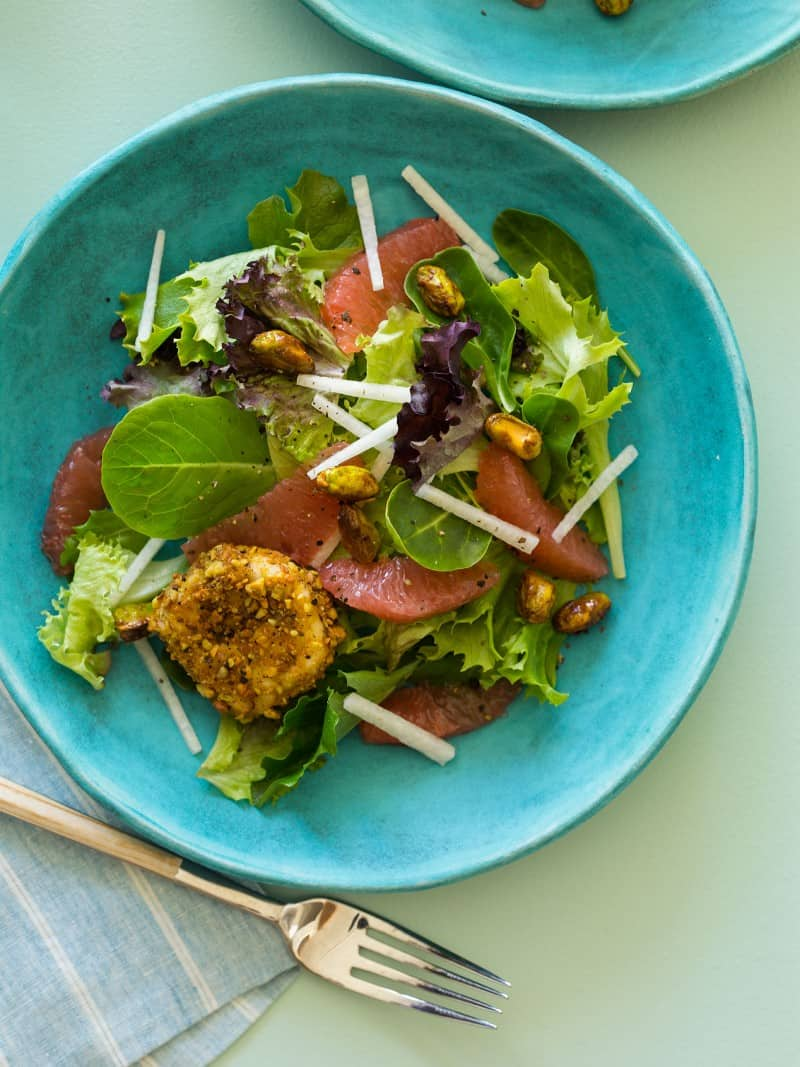 A recipe for Grapefruit and Mixed Green Salad with pistachio crusted goat cheese rounds.