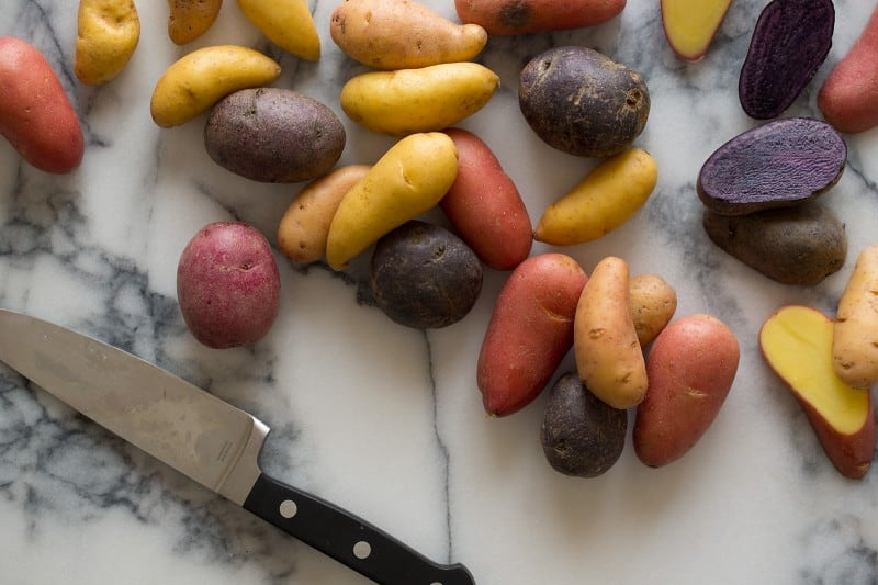 A close up of fingerling potatoes with a knife on a marble surface.