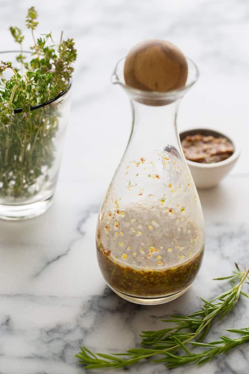 A close up of a bottle of mustard vinaigrette next to fresh herbs mustard.