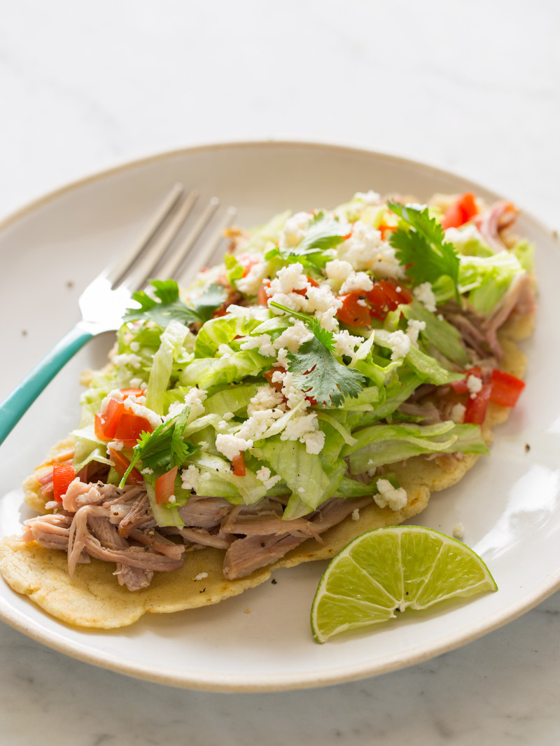 Huaraches with carnitas and fixings on a plate with a lime wedge and a fork.