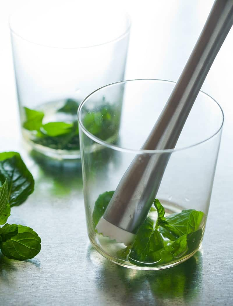 Muddled mint leaves for a Honey Rum Fizz