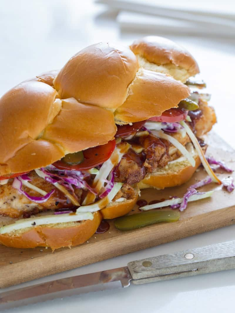 A fried chicken sandwich on a wooden board with a knife.