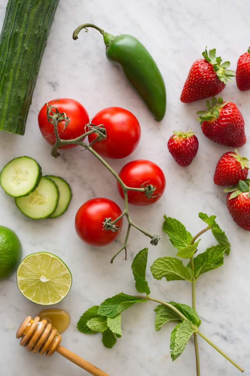Fresh ingredients for strawberry tomato gazpacho on a marble surface.