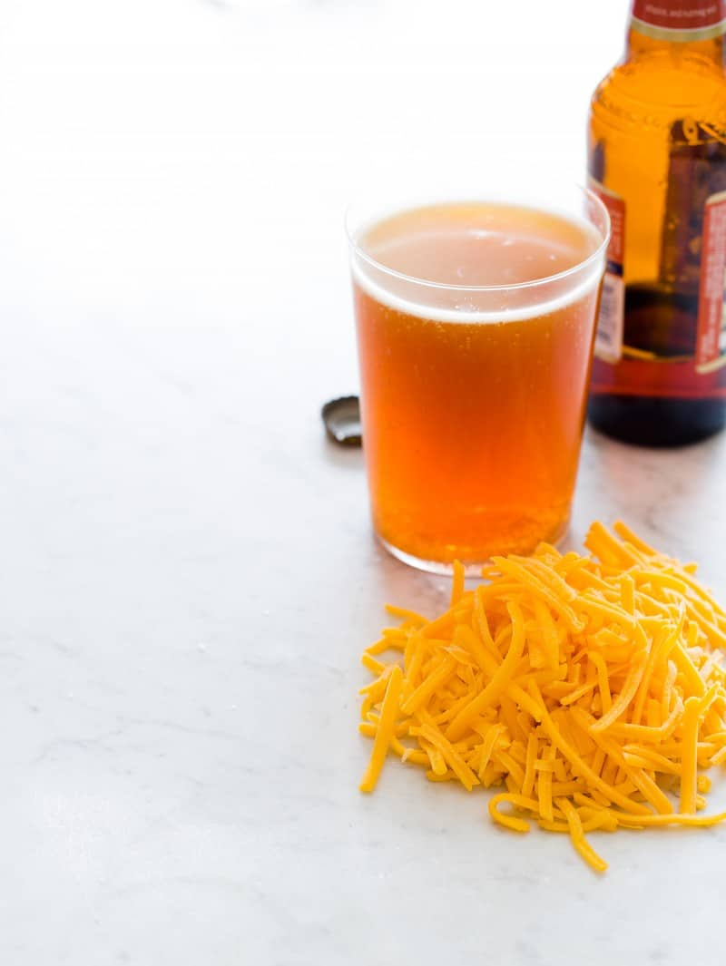 A glass and a bottle of beer next to a pile of shredded cheese.