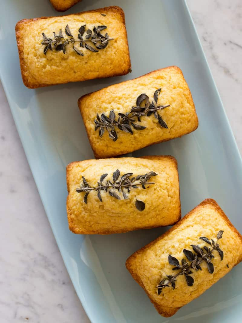 A close up of a platter of individual cornbread loaves with baked in oregano on top.