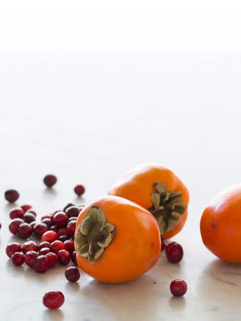 A close up of fresh cranberries and persimmons for spiced chutney.