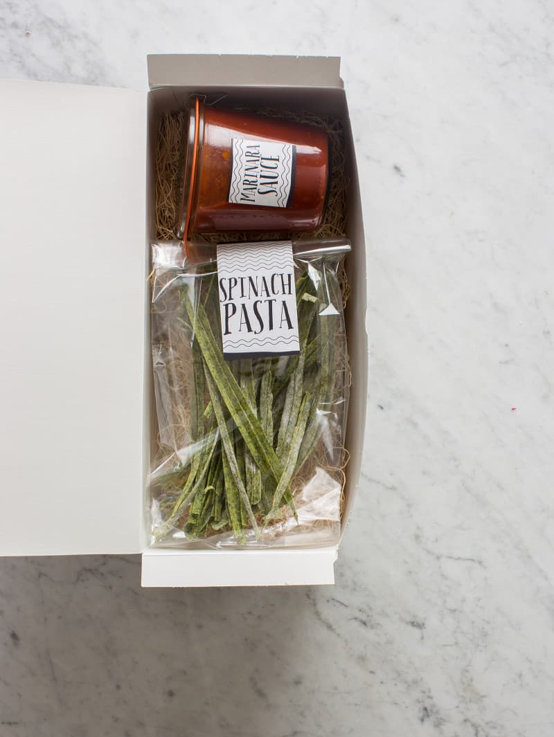 Clear labeled bag of homemade pasta with a labeled jar of sauce in a gift box.