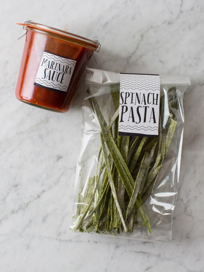 Clear labeled bag of homemade pasta with a labeled jar of sauce.