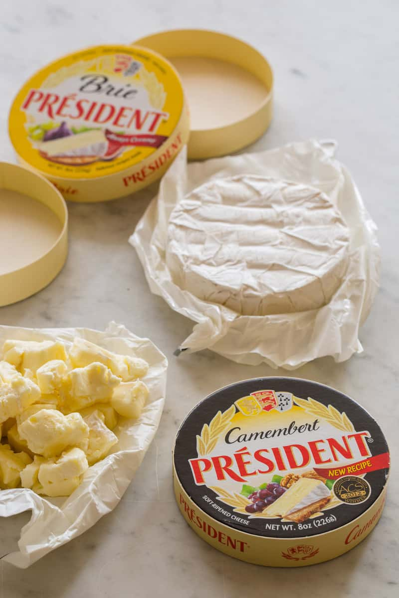 Boxes and open containers of different cheeses for creamy skillet mac and cheese.