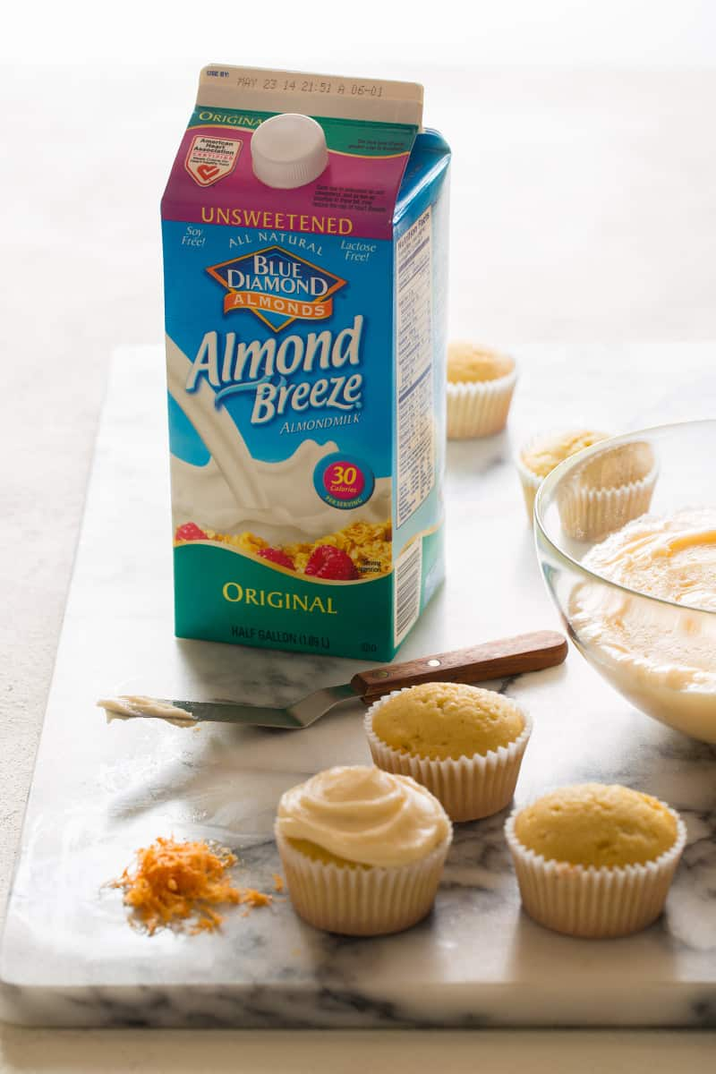 A carton of Blue Diamond almond milk next to butter cupcakes being frosted.