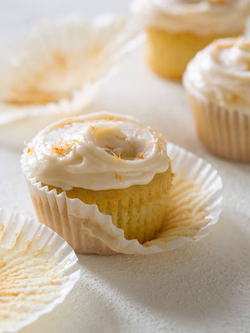 A close up of a butter cupcake with grapefruit buttercream half out of the cupcake wrapper.