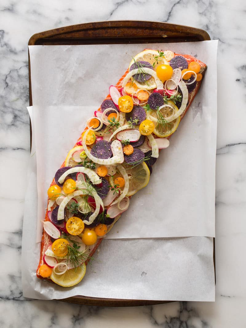 A whole side of salmon stacked with veggies and herbs on parchment paper.