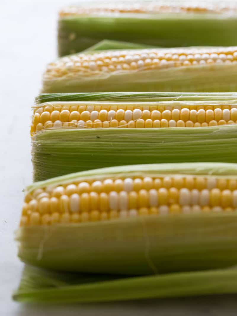 A close up of several fresh corn on the cobs with some husk still on.