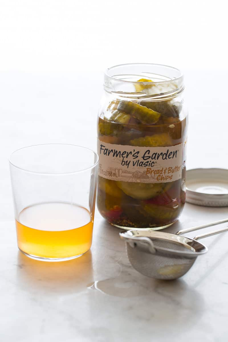 A jar of bread and butter chip pickles with a glass of juice and a strainer.