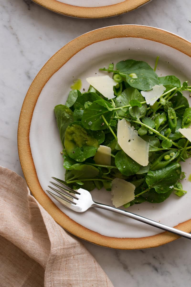 A close up of a plate of watercress salad with green apple vinaigrette and a fork.