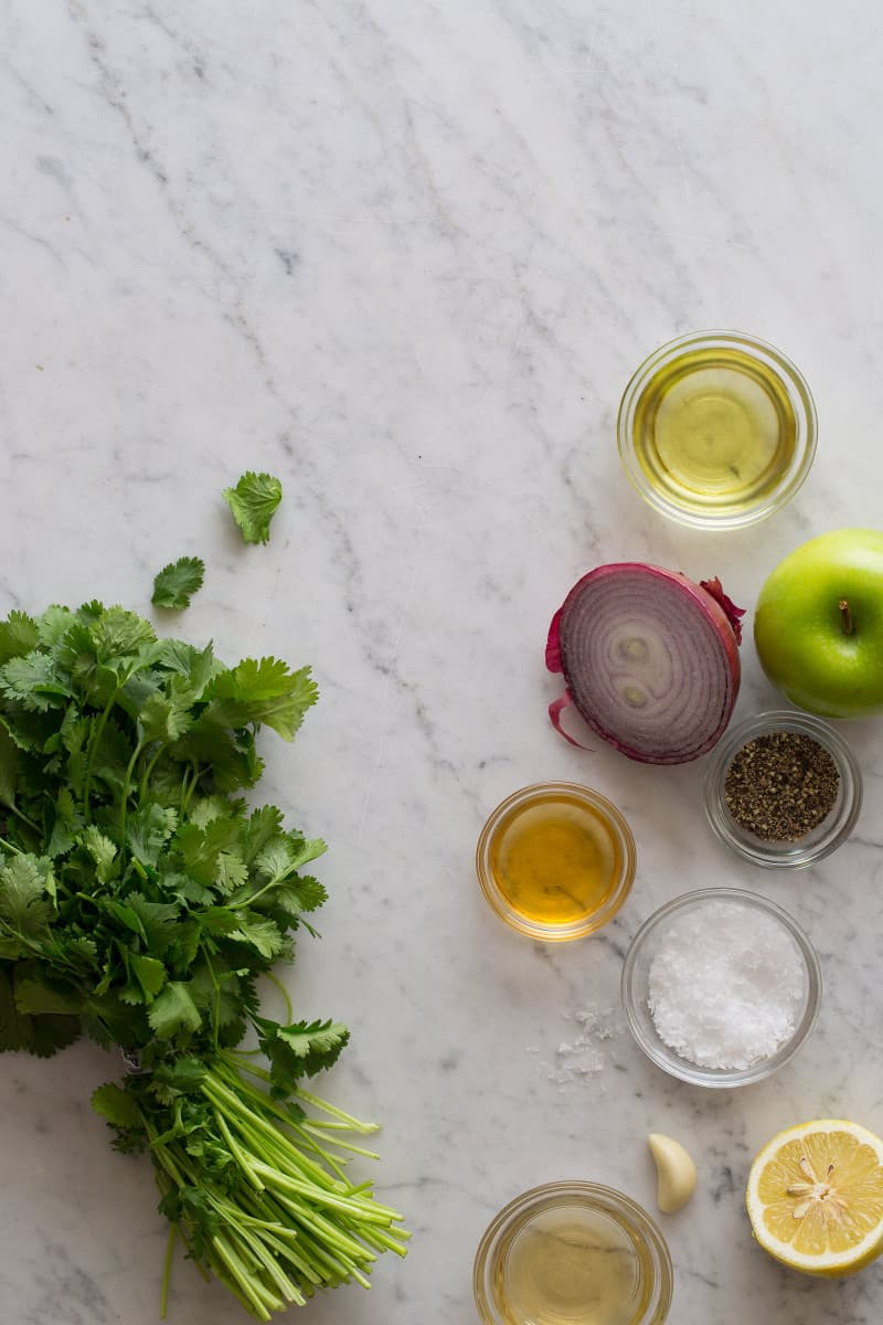 Ingredients for green apple vinaigrette on a marble countertop.