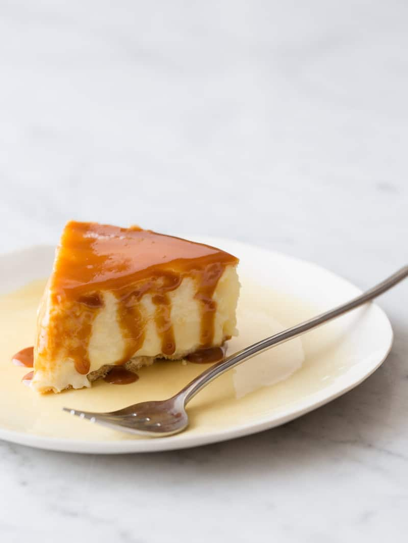 A piece of New York style cheesecake with cajeta drizzled on top with a fork.
