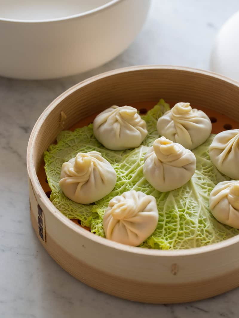 A close up of a steamer full of shanghai soup dumplings before being steamed.