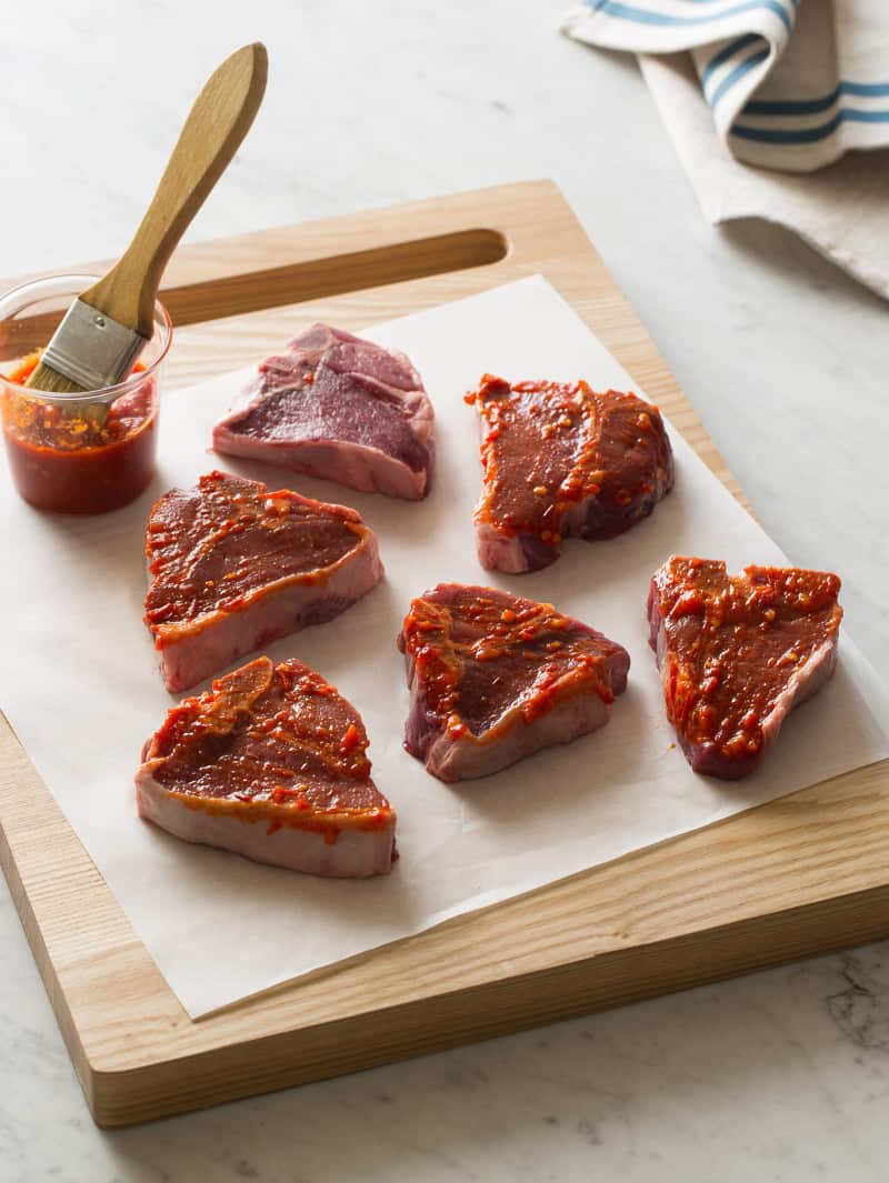A wooden cutting board of raw lamb chops being brushed with sauce.