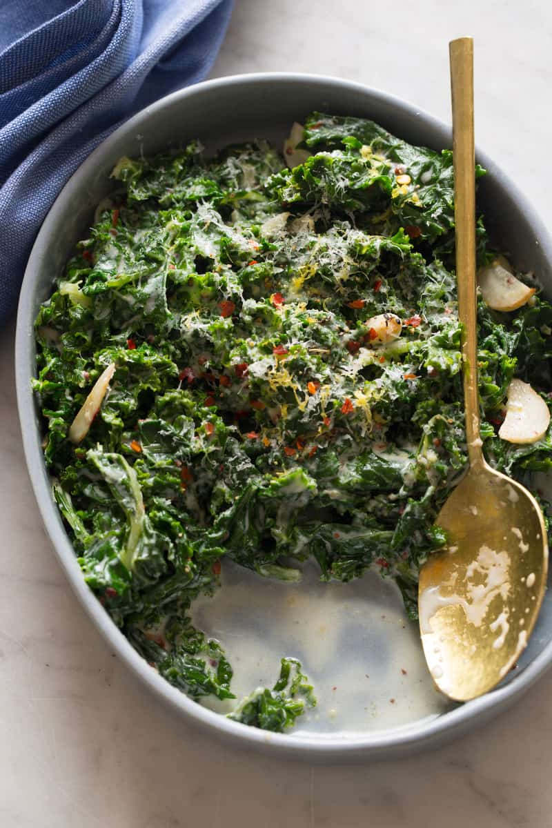 A close up of a dish of creamed kale with servings taken out and a spoon.