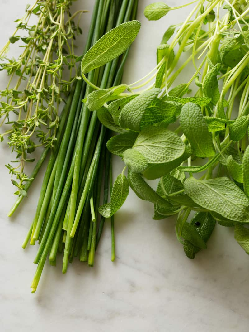 A close up of a variety of fresh green herbs for creamy potato salad.