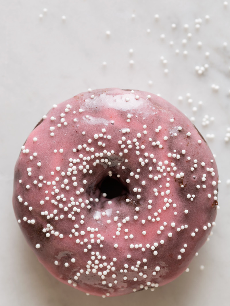 A close up of a chocolate and cardamom baked doughnut with sweet plum glaze and sprinkles.