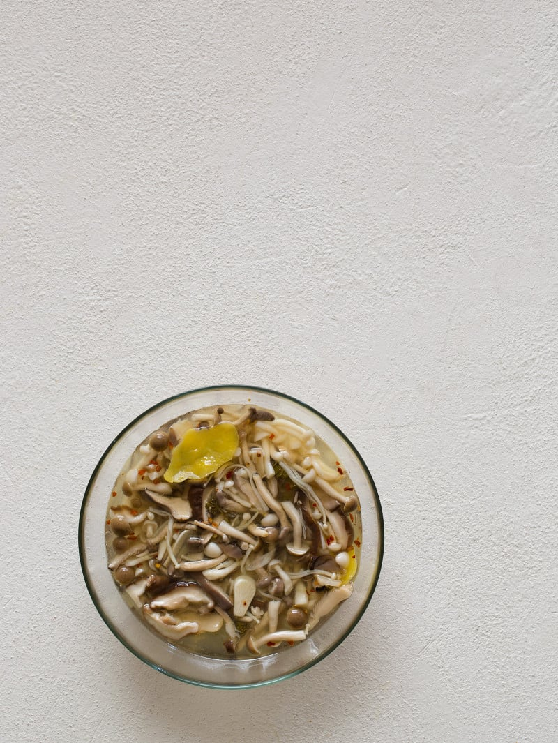A clear mixing bowl of fresh mushrooms in brine.