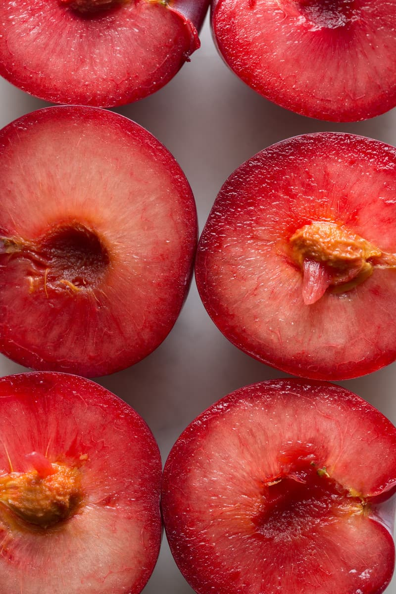 A close up of the flesh of halved fresh sweet plums.