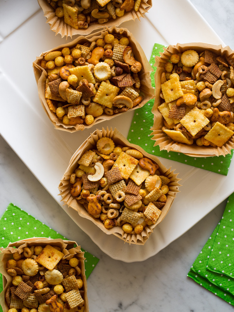 Wood and paper containers full of snack mix on a platter with green paper napkins.
