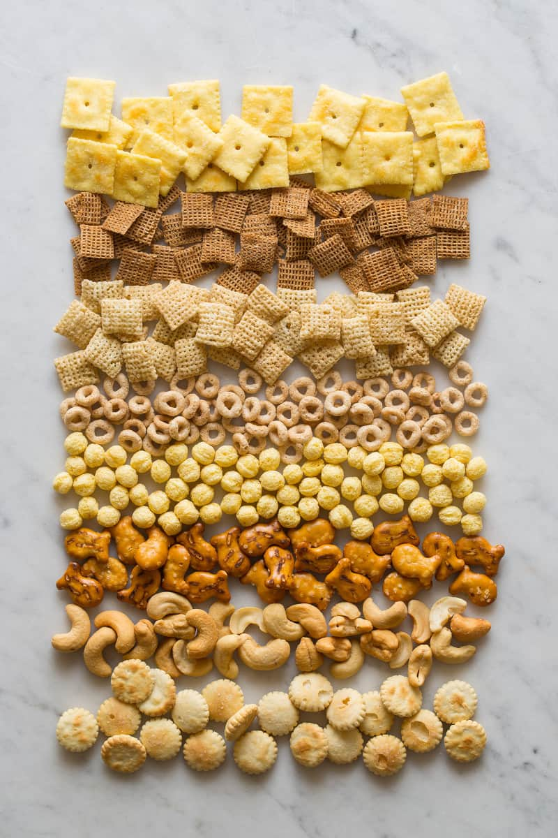 Cereals, crackers, and nuts for snack mix on a marble surface.