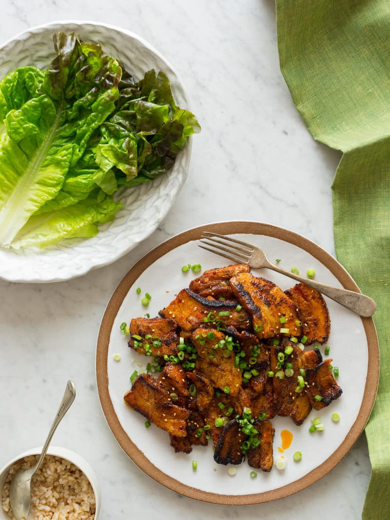 A plate of Korean style marinated spicy pork belly next to a plate of lettuce.