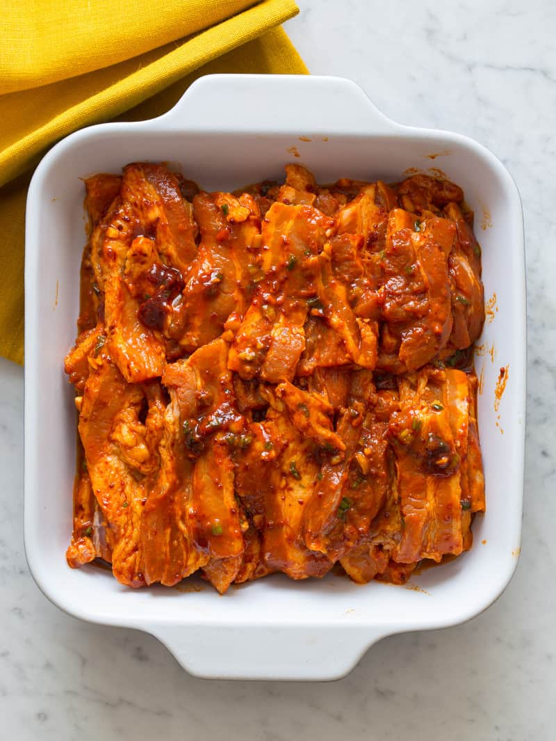Korean style marinated spicy pork belly in a baking dish.