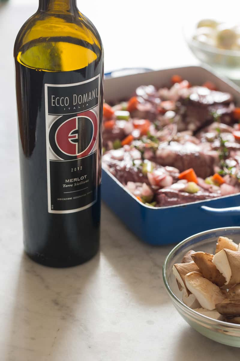 A pan of marinading chicken and vegetables with a wine bottle and a bowl of mushrooms.