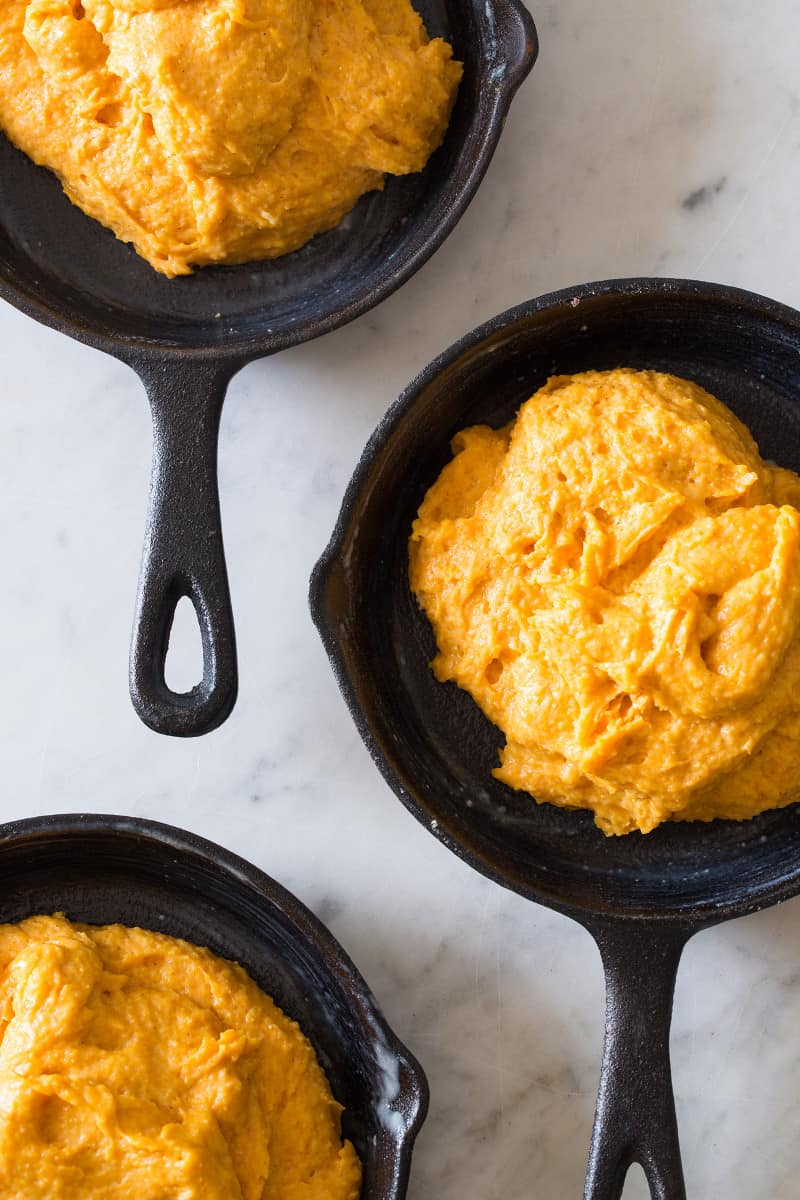 A close up of pumpkin cornbread  batter in cast iron skillets.