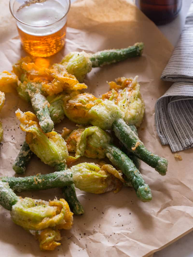 A close up of stuffed and fried squash blossoms with a drink.