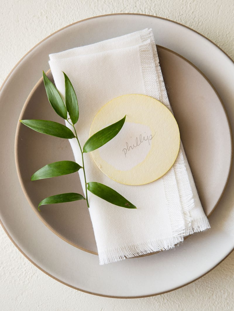 A place setting with a DIY dip dye place card and a sprig of leaves.